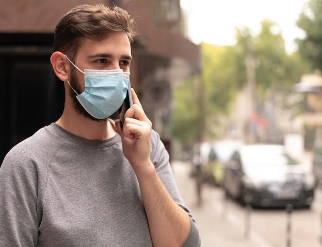 Mann, der draußen am telefon spricht, während er eine medizinische maske trägt