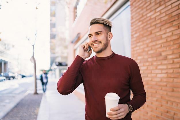 Mann, der draußen am telefon spricht.