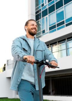 Mann, der draußen einen umweltfreundlichen roller fährt