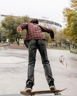 Mann, der draußen im stadtpark skateboarding genießt