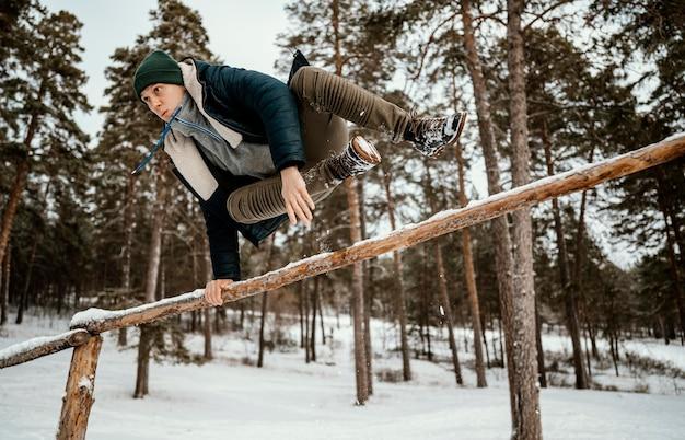 Mann, der draußen im winterschnee springt