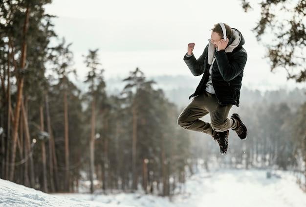 Mann, der draußen in der natur während des winters mit kopienraum springt