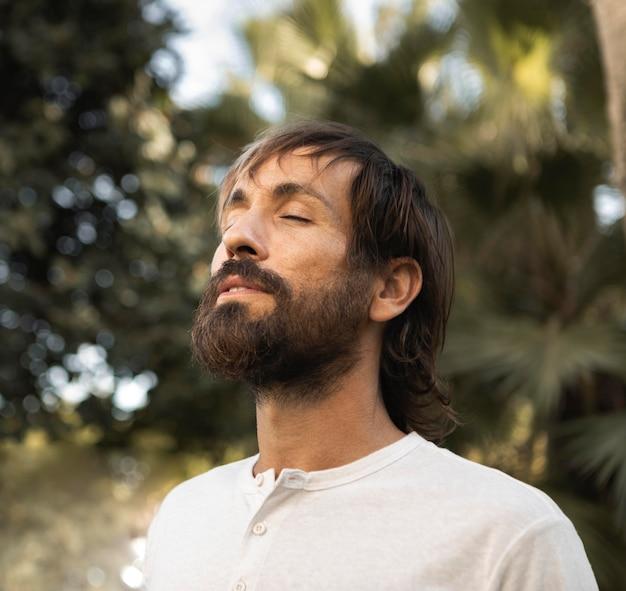 Mann, der draußen meditiert, während er yoga macht