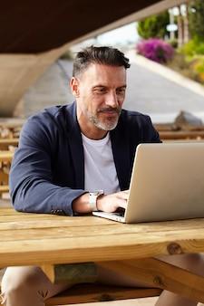 Mann, der draußen mit seinem computer arbeitet