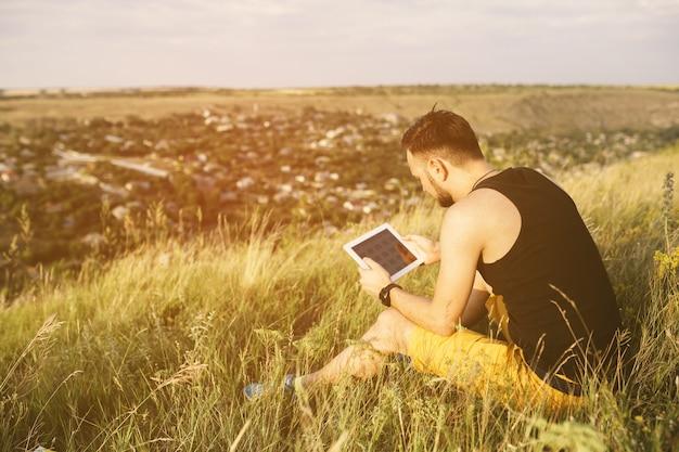 Mann, der draußen mit tablettenauflage arbeitet. retro vintage instagram filter