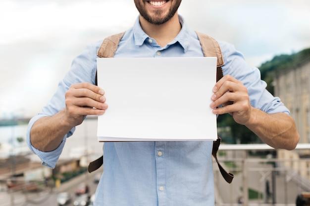 Mann, der draußen weißes schwarzes papier zeigt