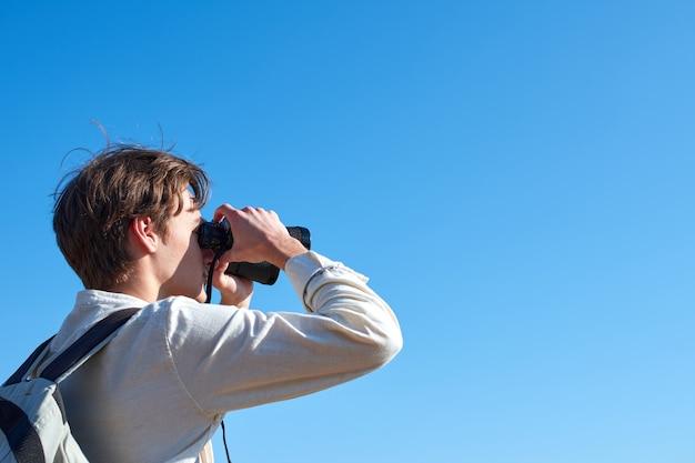Mann, der durch fernglas auf einem blauen himmel schaut