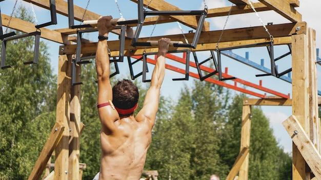 Mann, der durch hürden während des hindernislaufs im schuh- oder sportwettbewerb geht