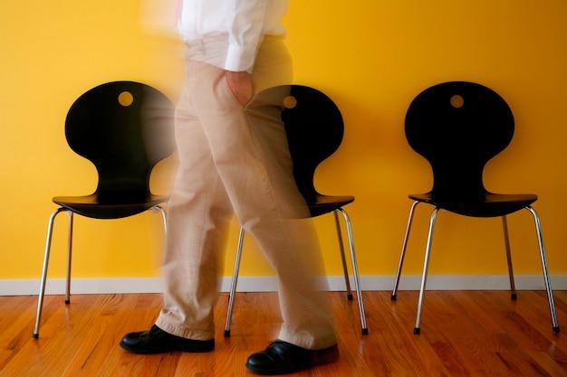 Mann, der durch stühle, niedriger abschnitt steht