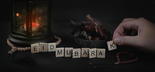 Mann, der eid mubarak gruß-scrabble-buchstaben anordnet