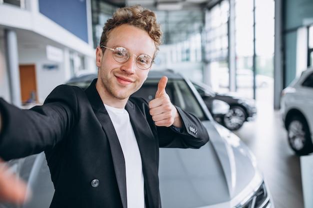 Mann, der ein auto an einem ausstellungsraum kauft
