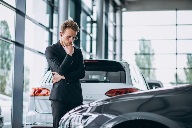 Mann, der ein auto betrachtet und an einen kauf denkt