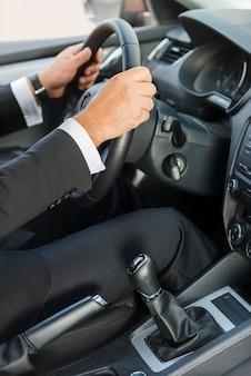 Mann, der ein auto fährt. nahaufnahme des mannes in formaler kleidung, die auto fährt