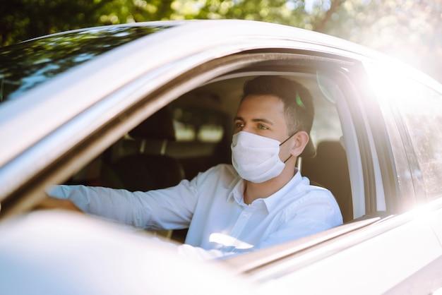 Mann, der ein auto fährt, setzt eine medizinische maske während einer epidemie in der quarantänestadt auf.