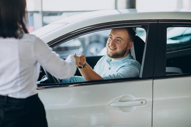Mann, der ein auto in einer autosalon wählt