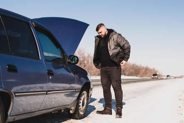 Mann, der ein auto steht an der haube repariert