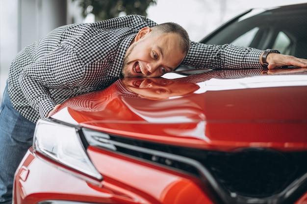 Mann, der ein auto umarmt