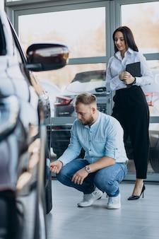 Mann, der ein auto wählt und mit verkäufer spricht