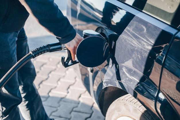 Mann, der ein auto während niedriger kraftstoffraten, kraftstoffpreise, transportkonzept tankt