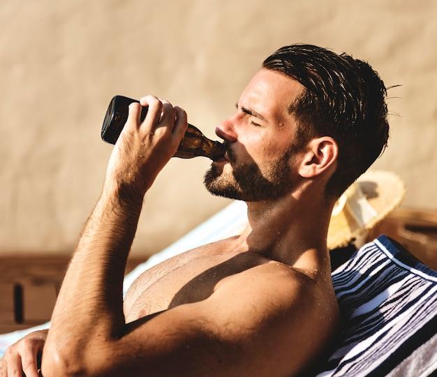 Mann, der ein bier am pool trinkt