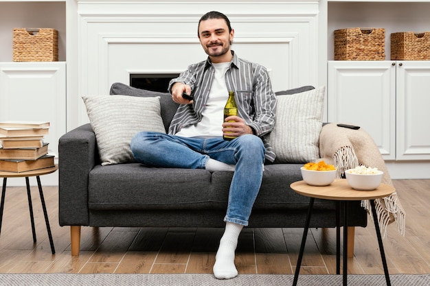 Mann, der ein bier genießt und fernsehen sieht, das auf der couch sitzt