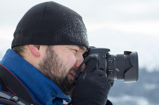 Mann, der ein bild mit seiner kamera im winter macht.