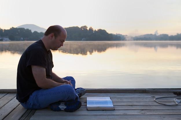 Mann, der ein buch auf einer hölzernen brücke liest, die durch hügel und einen see unter dem sonnenlicht umgeben ist