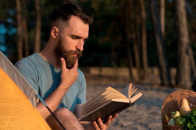 Mann, der ein buch denkt und liest