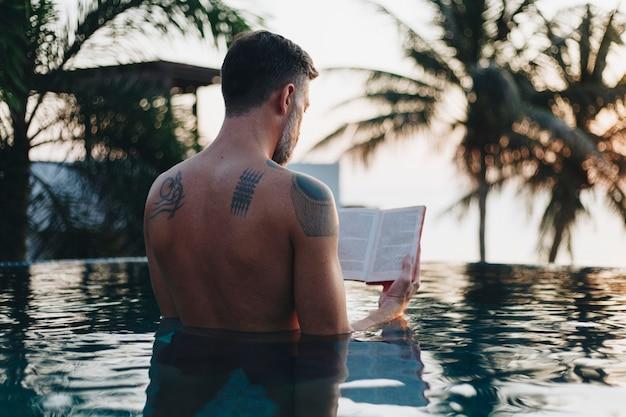 Mann, der ein buch im swimmingpool liest