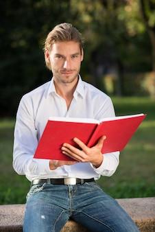 Mann, der ein buch in einem park liest