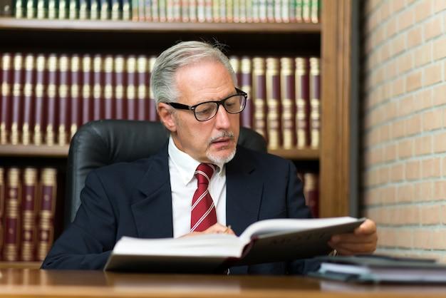 Mann, der ein buch in seiner bibliothek liest