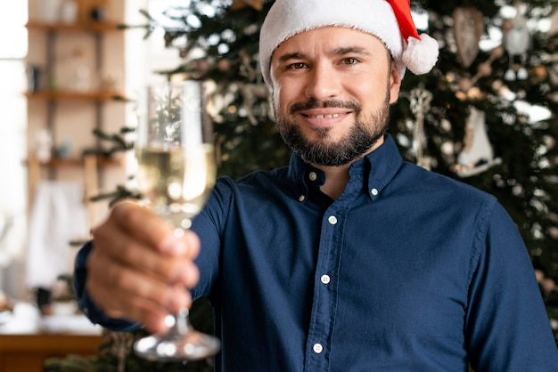Mann, der ein champagnerglas am weihnachtstag hält