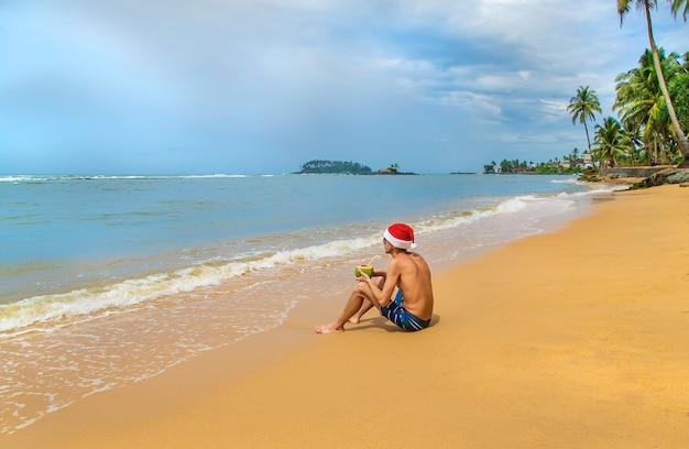 Mann, der ein cocktail mit sankt-hut auf dem strand trinkt