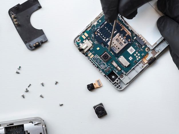 Mann, der ein defektes telefon repariert