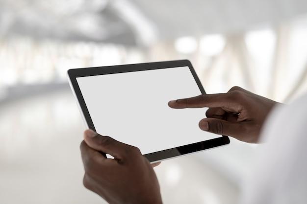 Mann, der ein digitales tablet mit weißem bildschirm hält
