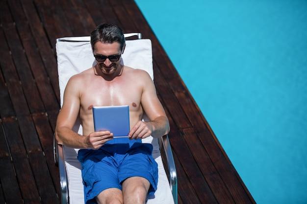 Mann, der ein digitales tablett nahe dem pool verwendet