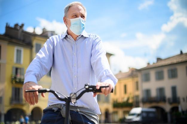 Mann, der ein e-bike benutzt und einen mak wegen eines coronavirus-pandemie-notfalls trägt