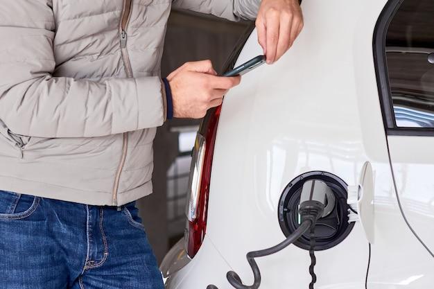 Mann, der ein elektroauto an der öffentlichen ladestation auflädt und mit seinem smartphone bezahlt. null-emissions-konzept