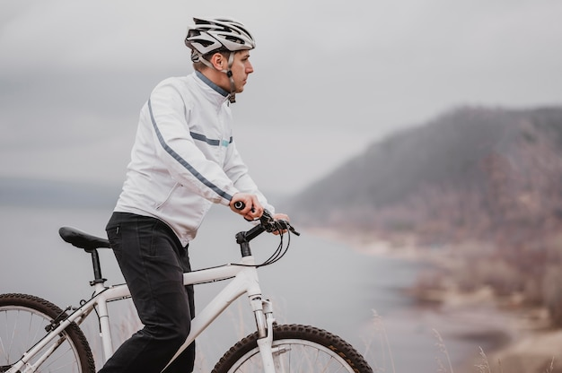 Mann, der ein fahrrad an einem kalten tag reitet und mit kopierraum wegschaut