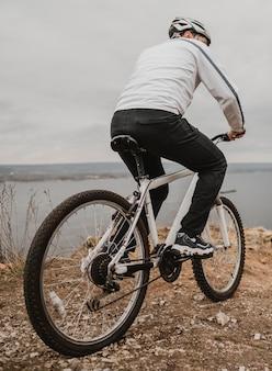 Mann, der ein fahrrad draußen reitet