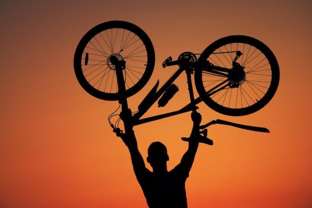 Mann, der ein fahrrad gegen den sonnenunterganghintergrund hält