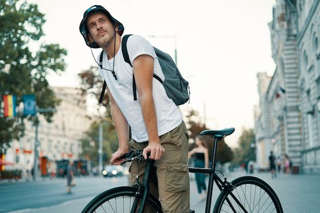 Mann, der ein fahrrad in einer alten europäischen stadt im freien fährt