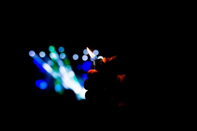 Mann, der ein feuerzeug in einem nachtkonzert anhält