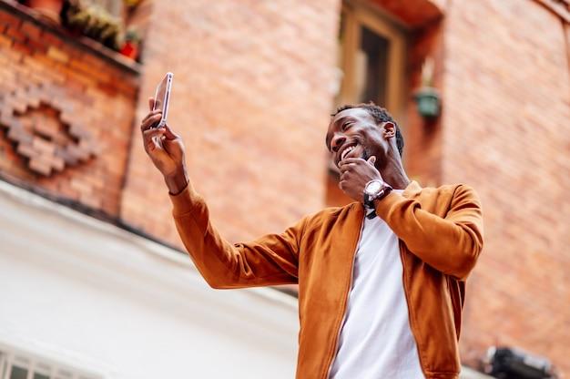 Mann, der ein foto mit handy macht und sein gesicht berührt