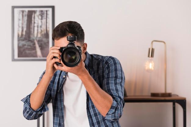 Mann, der ein foto mit seiner kamera macht