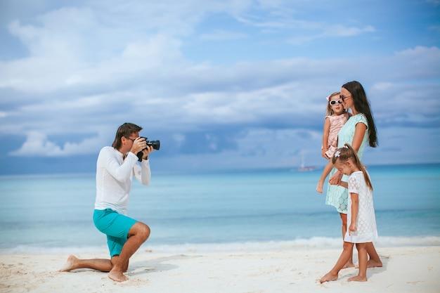 Mann, der ein foto seiner familie am strand macht
