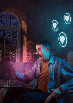 Mann, der ein gadget verwendet und nachts zu hause neon-benachrichtigungen erhält