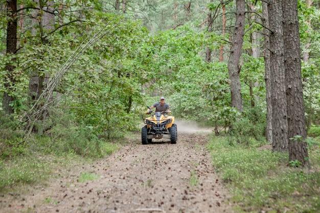 Mann, der ein gelbes quad-atv-geländefahrzeug auf einem sandigen wald reitet. extremsportbewegung, abenteuer, touristenattraktion.