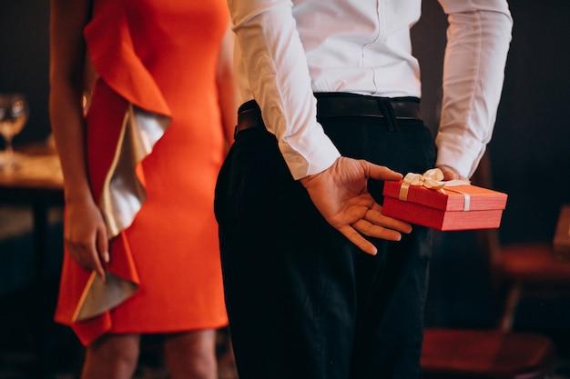 Mann, der ein geschenk für seine freundin am valentinstag hält