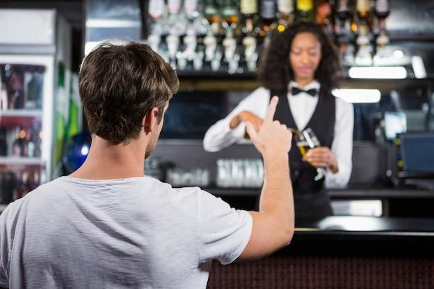 Mann, der ein getränk am bartresen in der bar bestellt